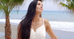 Portrait of Smiling Woman on Tropical Beach. Waist Up Portrait of Attractive Smiling Woman with Long Dark Hair Laughing at Camera with View of Tropical Beach and stock video