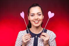 Portrait of smiling woman with two hearts from papper in hands. On dark red background Stock Photography