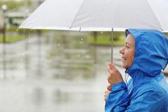Portrait of smiling woman under umbrella in rain. Portrait of smiling woman under umbrella in rain Royalty Free Stock Photography