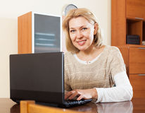 Portrait of a smiling  woman using laptop at home Stock Photos