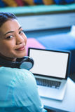 Portrait of smiling woman using laptop in library Royalty Free Stock Photo