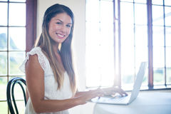 Portrait of smiling woman using a laptop in restaurant Stock Photography