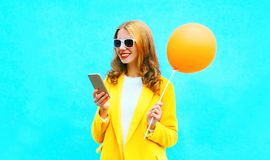 Portrait smiling woman using smartphone holds an air balloon Royalty Free Stock Photos