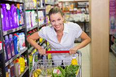 Portrait of smiling woman walking in aisle with his trollet Stock Images