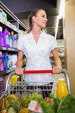 Portrait of smiling woman walking in aisle with his trollet Royalty Free Stock Photo