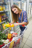 Portrait of smiling woman walking with his trolley on aisle Royalty Free Stock Photo