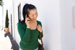 Smiling woman walking outside and talking on mobile phone Royalty Free Stock Photos