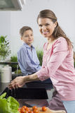 Portrait of smiling woman washing hands with son sitting on counter in kitchen Stock Photos
