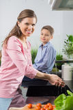Portrait of smiling woman washing hands with son sitting on counter in kitchen Royalty Free Stock Photography