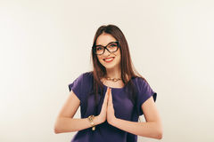 Portrait of a smiling woman wearing eye glasses. The palms together.  Royalty Free Stock Images
