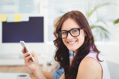Portrait of smiling woman wearing eyeglasses while holding smartphone at desk. In office Royalty Free Stock Photography