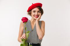 Portrait of a smiling woman wearing red beret. Holding a rose and looking at camera isolated over white background Stock Photos