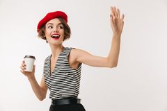 Portrait of a smiling woman wearing red beret. Holding cup of coffee and waving with hand isolated over white background Royalty Free Stock Photography