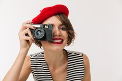 Portrait of a smiling woman wearing red beret. Taking picture with a photo camera isolated over white background Royalty Free Stock Photo