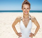 Portrait of smiling woman in white swimsuit at sandy beach. Heading to white sand blue sea paradise. Portrait of smiling woman in white swimsuit at sandy beach Royalty Free Stock Images