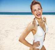 Portrait of smiling woman in white swimsuit at sandy beach. Heading to white sand blue sea paradise. Portrait of smiling woman in white swimsuit at sandy beach Royalty Free Stock Image
