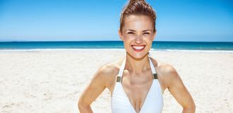 Portrait of smiling woman in white swimsuit at sandy beach. Heading to white sand blue sea paradise. Portrait of smiling woman in white swimsuit at sandy beach Royalty Free Stock Photo