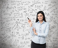 Portrait of smiling woman who points out complicated math calculations. Royalty Free Stock Photo
