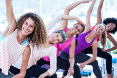 Portrait of smiling women bending with arms raised Royalty Free Stock Images