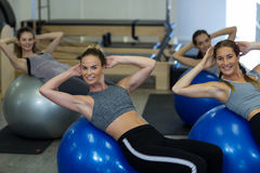 Portrait of smiling women exercising with fitness ball Stock Photos