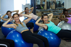 Portrait of smiling women exercising with fitness ball Royalty Free Stock Images