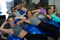 Portrait of smiling women exercising with fitness ball Royalty Free Stock Photo