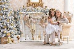 Woman and girl  decorating Christmas tree together. Portrait of smiling women and girl  decorating Christmas tree together Royalty Free Stock Photography