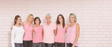 Composite image of portrait of smiling women supporting breast cancer social issue stock photography