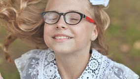 Portrait of a smiling 13 year old girl put on glasses. Face close up. stock footage