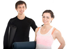 Portrait of smiling yogi couple with yoga mats royalty free stock images
