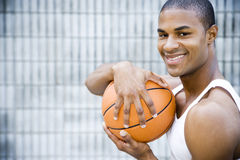 Portrait of a smiling young African American man holding a basketball. Royalty Free Stock Image