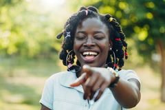 Portrait of a smiling young African black woman looking and showing a finger to the camera. copy space stock photos