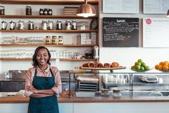 Smiling young African entrepreneur standing at her bakery counter. Portrait of a smiling young African female entrepreneur standing with her arms crossed at the Royalty Free Stock Photos