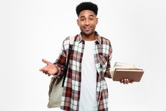 Portrait of a smiling young african male student. Dressed in plaid shirt with a backpack holding books and looking at camera isolated over white background Stock Photo