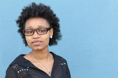 Portrait of smiling young african woman with afro and glasses. Copy space on the left side of the image.  Stock Images