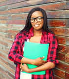 Portrait smiling young african woman in glasses holding folder over background. Portrait smiling young african woman in glasses holding folder over wooden Stock Image