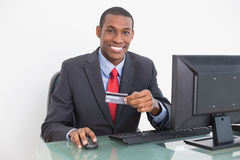 Portrait of a smiling young Afro businessman doing online shopping Stock Images