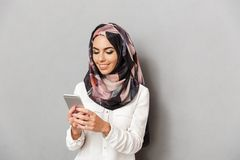 Portrait of a smiling young arabian woman. Holding mobile phone isolated over gray background Royalty Free Stock Photo