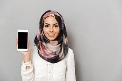 Portrait of a smiling young arabian woman. Showing blank screen mobile phone isolated over gray background Royalty Free Stock Photos