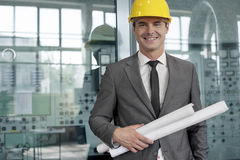 Portrait of smiling young architect holding rolled up blueprints in industry Stock Photos