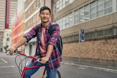 78ac66e53 Smiling young man standing with his bicycle in the city royalty free stock  photos