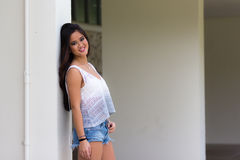 Portrait of a smiling young Asian woman in jeans shorts Royalty Free Stock Photo