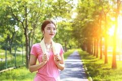 Young asian women runner preparing for jogging. Portrait of a smiling young asian woman runner preparing for jogging in city park stock image
