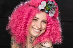 Portrait of smiling young attractive caucasian girl model with afro style curly bright pink hair, tattooed face and flowers woven. Into her hair. Photo in the stock image