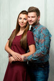 Portrait of smiling young attractive couple hugging. Portrait of smiling young attractive couple in maroon dress and blue shirt hugging Stock Images