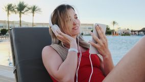 Portrait of smiling young attractive young woman in red bikini listening music from her smartphone in white headphones stock video footage