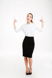 Portrait of a smiling young beautiful businesswoman pointing fingers up Stock Photo