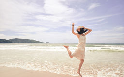 Portrait of smiling young beautiful woman jumping on the beach Stock Photo