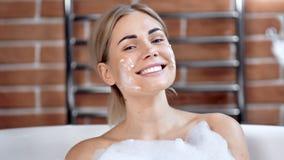 Portrait of smiling young beautiful woman with mask on face making splash taking foam bath. Close-up charming girl having fun relaxing enjoying beauty stock video