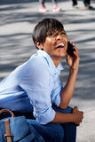 Smiling young black lady sitting outside and talking on cell phone Stock Images